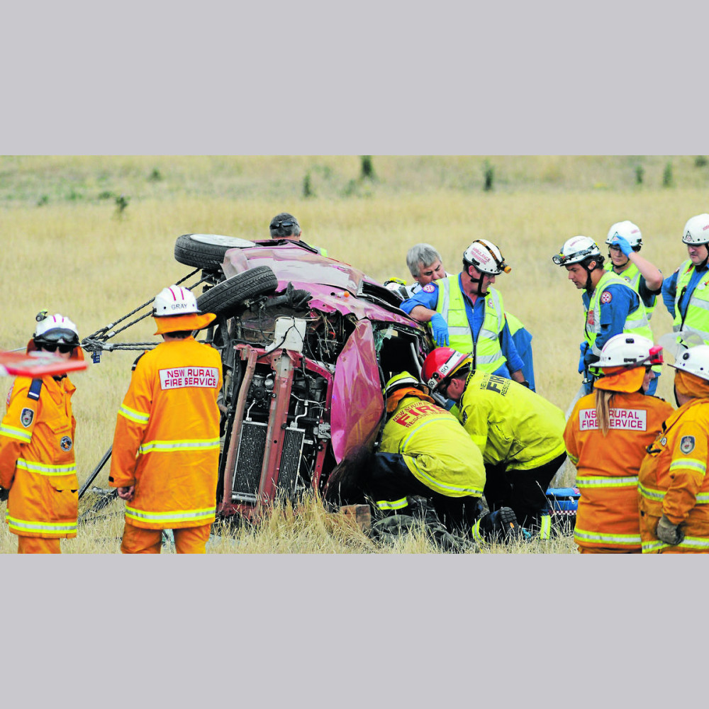LIFESAVERS: Paramedics and firefighters rescue a 23-year-old-woman trapped in her car off Molong Road. Photo: STEVE GOSCH